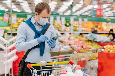 Young man poses in grocery store during coronavirus pandemic, wears protective medical mask and gloves, stands in supermarket near trolley, checks something in smartphone. Health, safety, quarantine Banque d'images