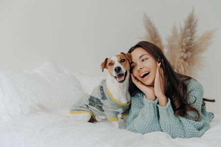 People and animals concept. Joyful pretty young woman express love to dog, spends leisure time with pet, lie together on bed, looks tenderly at animal, feels not bored with true loyal friend