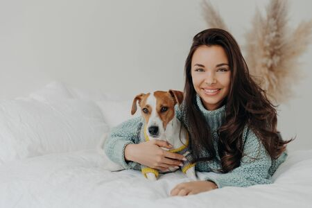 Photo of cheerful woman embraces dog with love, spend free time together, expresses tender feeling and emotions, falls in love with pet, lie on comfortable bed. Positive emotions, animals and care
