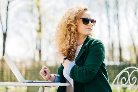 Young pretty female with fluffy blonde hair wearing sunglasses sitting on in the sun in front of laptop translating textes looking around noticing her best friend enjoying sunny weather in the yard Archivio Fotografico