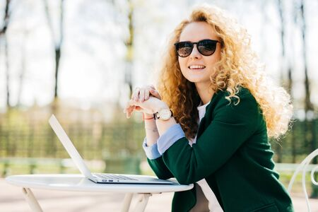 Beautiful young student female with beautiful curly blonde hair elegant dressed using generic laptop computer for writing essay having rest outdoors having charming smile looking into distance Archivio Fotografico