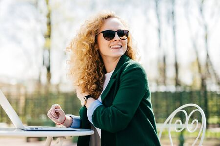Happy stylish woman with curly light hair wearing sunglasses working with laptop outside in park typing necessary documents turning back noticing someone at the street. Cheerful woman having rest Archivio Fotografico