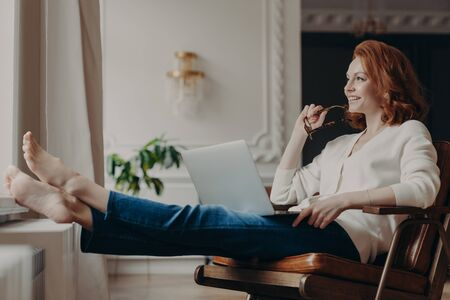 Thoughtful satisfied female freelancer works with computer at home, stretches legs and holds eyeglasses, searches information on social media sites, uses home internet connection for online chatting