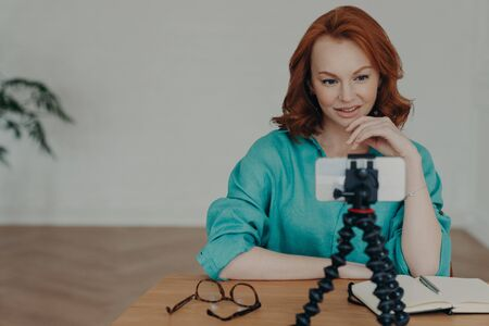 Photo of ginger female blogger shoots video of herself for personal blog, looks at camera of smartphone on tripod, chats with followers, works as freelance, earns money online, enjoys networking Archivio Fotografico