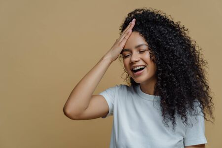 Horizontal shot of happy positive Afro American woman has fun, keeps hand on forehead, giggles happily, closes eyes, has bushy curly hair, wears casual white t shirt, isolated on beige background.