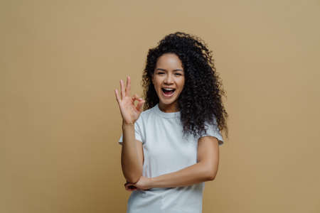 Photo of slim cheerful African American woman with curly hair, smiles happily, being in good mood, wears white t shirt and jeans, keeps hand in pocket, has slim figure, isolated on beige background 免版税图像 - 151087037