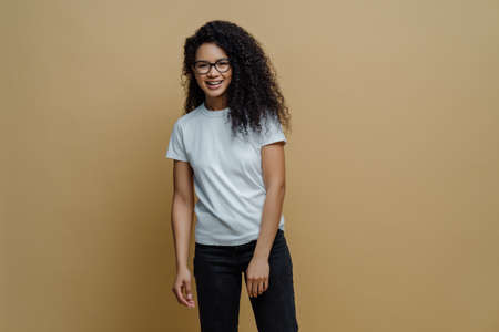 Photo of slim cheerful African American woman with curly hair, smiles happily, being in good mood, wears white t shirt and jeans, keeps hand in pocket, has slim figure, isolated on beige background 免版税图像 - 151087038