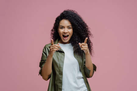 Photo of slim cheerful African American woman with curly hair, smiles happily, being in good mood, wears white t shirt and jeans, keeps hand in pocket, has slim figure, isolated on beige background 免版税图像 - 151087053