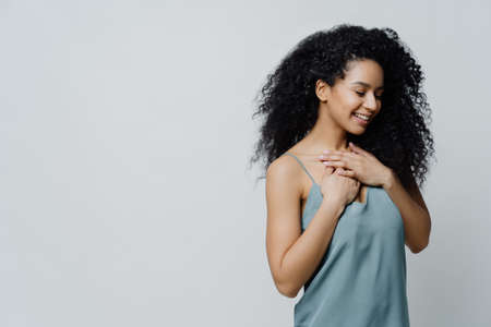 Photo of slim cheerful African American woman with curly hair, smiles happily, being in good mood, wears white t shirt and jeans, keeps hand in pocket, has slim figure, isolated on beige background 免版税图像 - 151087044