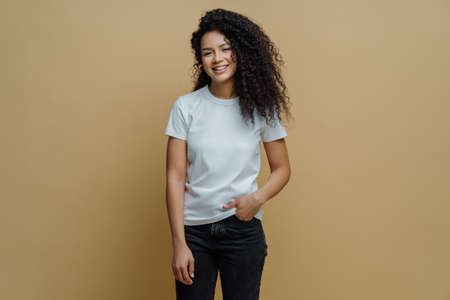 Photo of slim cheerful African American woman with curly hair, smiles happily, being in good mood, wears white t shirt and jeans, keeps hand in pocket, has slim figure, isolated on beige background