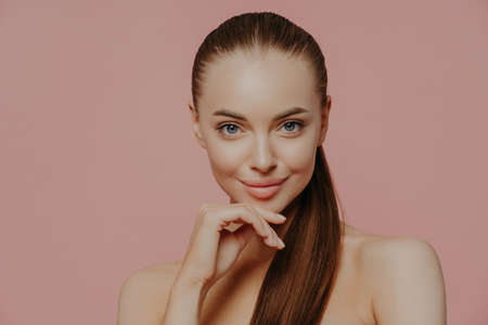 Confident brunette young woman keeps hand under chin