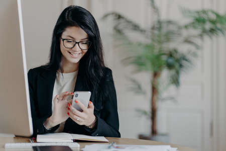 Beautiful smiling female freelancer works remotely, concentrated in smartphone, sends feedback on received message, sits in coworking space, dressed formally, works on computer, surfs internet