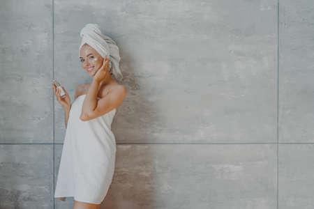 Happy healthy young woman with tender facial skin, applies beauty cream and undergoes beauty treatments, wrapped in bath towel, poses against gray background with copy space for your promotion Фото со стока