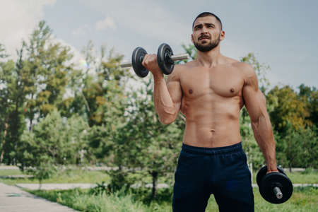 Horizontal shot of topless fitness unshaven European man has muscular body, raises barbells, wears shorts, demonstrates strong arms, has workout outdoor in park. Sportsman makes weightlifting