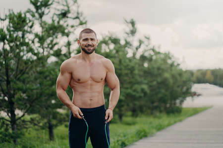 Cheerful unshaven sportsman skips with rope, has muscular body, enjoys fitness training, poses outdoor. Strong man with naked torso uses sport equipment for workout, breathes fresh air in nature