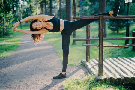 Active slim woman in sport clothes does pilates exercises and stretches outdoor, has glad expression, good flexibility, enjoys morning workout in fresh air. People, lifestyle, wellbeing concept