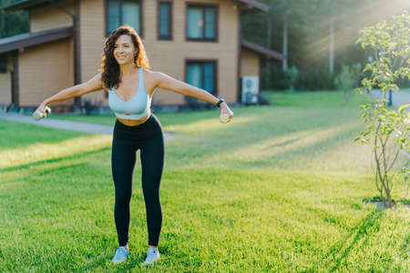 Slim motivated brunette woman dressed in cropped top and leggings, has workout with dumbbells, poses on green lawn near private house, has perfect body shape. Healthy lifestyle and sport concept
