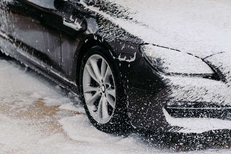 Car wash concept. Close up shot of dirty black car covered with white foam at cleaning station. Washing process. Perfect service