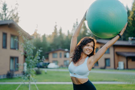 Active slim dark haired young woman with perfect body keeps big fitness ball over head, looks away with smile, dressed in active wear, poses outdoor near house, has yoga exercises in open air 版權商用圖片
