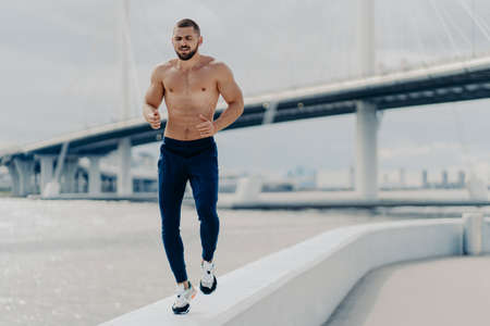 Active bearded male jogger runs along river side has workout outdoor dressed in active wear prepares for sport competitions has muscular strong body breathes fresh air. Sporty lifestyle concept