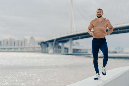 Motivated healthy bearded jogger runs early in morning near river, demonstrates determination, has muscular body, dressed in active wear, breathes fresh air. Healthy lifestyle and endurance concept