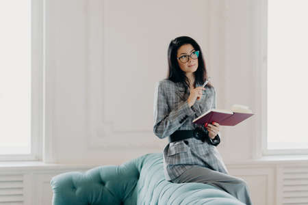 Serious businesswoman dressed in formal wear, concentrated into distance, ponders on creative ideas, writes down notes in notepad, wears spectacles, poses on back of couch in spacious light room