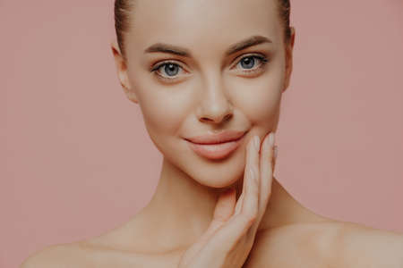 Cropped shot of attractive calm woman touches face gently, has direct gaze at camera, cares about skin, has well groomed skin, enjoys facial skin care, stands against pink studio background