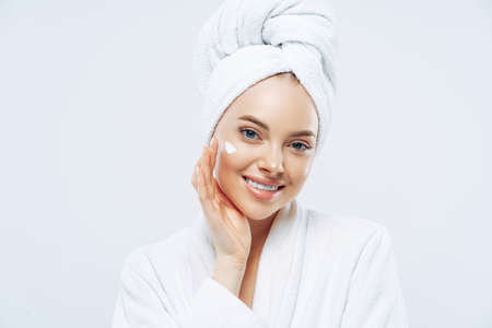 Charming relaxed beauty woman applies face cream, cares about complexion, touches cheek with hand, smiles gently at camera, dressed in bath robe, wrapped towel on washed hair, isolated on white Standard-Bild