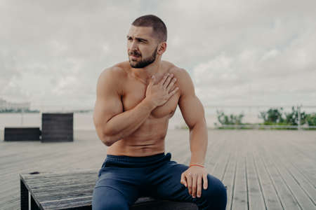 Thoughtful bearded man has rest after intensive cardio training, keeps hand on chest and has shortage of breathing, sits outdoor, concentrated aside, poses topless. Sport and healthy lifestyle