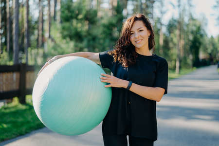 Fitness, sport and healthy lifestyle concept. Smiling curly brunette woman in black t shirt holds big fitness ball poses outside against forest background, breathes fresh air during sunny day Banco de Imagens