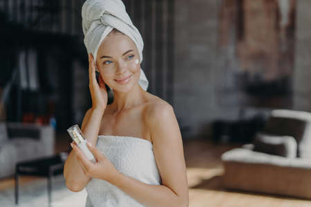 Pleased lovely young European woman applies body lotion wrapped in bath towel looks away with thoughtful expression stands indoor against blurred background in living room. Skin care concept