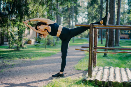 Outdoor shot of active slim young woman does stretching exercise, leans aside, keeps hands together, dressed in sportswear, breathes fresh air, leads active lifestyle. Sport and wellness concept