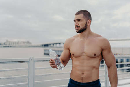 Muscular build bearded man goes in for sport, holds bottle of fresh water, focused into distance, poses on bridge near river during cloudy day, takes break after physical exercises. Cardio workout