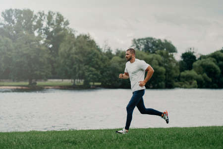 Sporty European man dressed in t shirt, trousers and sneakers and runs along river, trains outdoors, leads active lifestyle, breathes fresh air. People, sport, wellness and recreation concept. Banco de Imagens