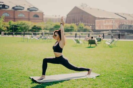 People sport and recreation concept. Sporty woman has healthy body raises arms exercises on karemat outdoors wears cropped top and leggings enjoys workout outside. Sportswoman in good shape.
