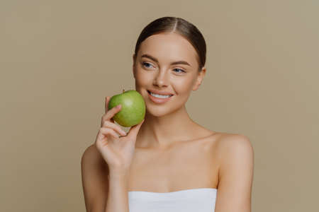 Thoughtful charming European woman holds apple near face smiles gently has white perfect teeth healthy clean skin wrapped in shower towel stands with shoulders against brown background. Foto de archivo