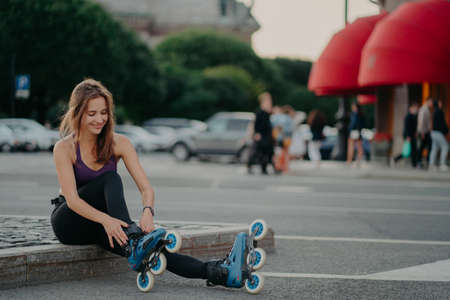 Sporty lifestyle and hobby. Pleased dark haired European woman puts on inline skates going rollerblading poses against blurred city background keeps fit spends free time actively. Outdoor shot