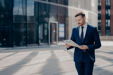 Focused bearded young businessman in formal outfit walking alone with newspaper in hands, reading latest news on his way to workplace with office buildings in background Banque d'images