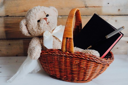 teddy bear in basket with book and pen wood background