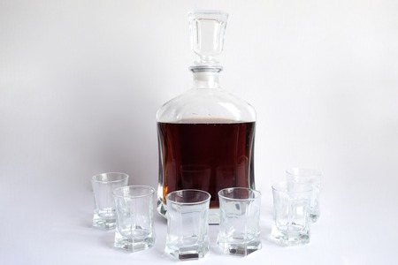Decanter and six glasses with empty whiskey white background