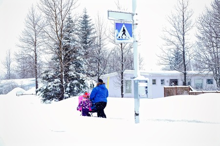 Mother and daughter carry the baby in a stroller through the snow