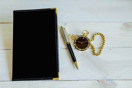 notebook black color with pen and pocket watch
