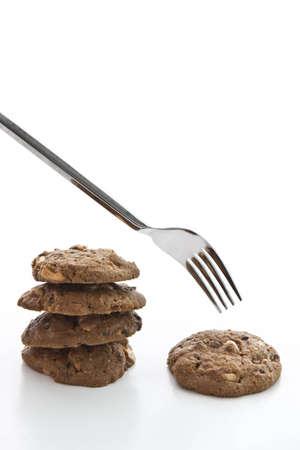 gordo y flaco: Comer galletas con un tenedor, la comparaci�n sobre el consumo de grasa fina Foto de archivo