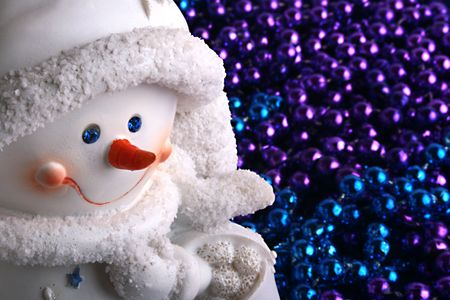 Ceramic snowball against a dark blue and violet beads for a fur-tree. photo