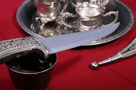 Dagger and silver glass with wine on a red background. Stock Photo - 5431709