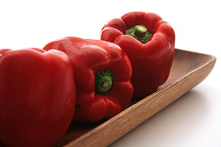 Three red pepper on a wooden plate - salad components.