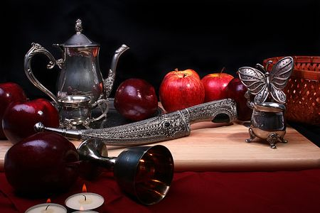 Dagger and silver glass with wine on a red background.