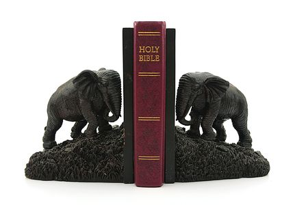 figurines: Decorative figurines of elephants support the Bible. Stock Photo