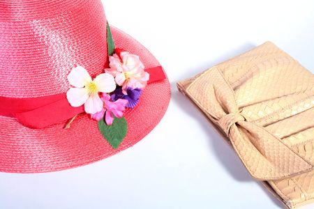 Female straw red hat with a flower and a handbag from a skin. Stock Photo