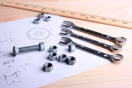 schemes: Set of wrenches, nuts and a bolt against the drawing of a nut and rolls of schemes. Working conditions.